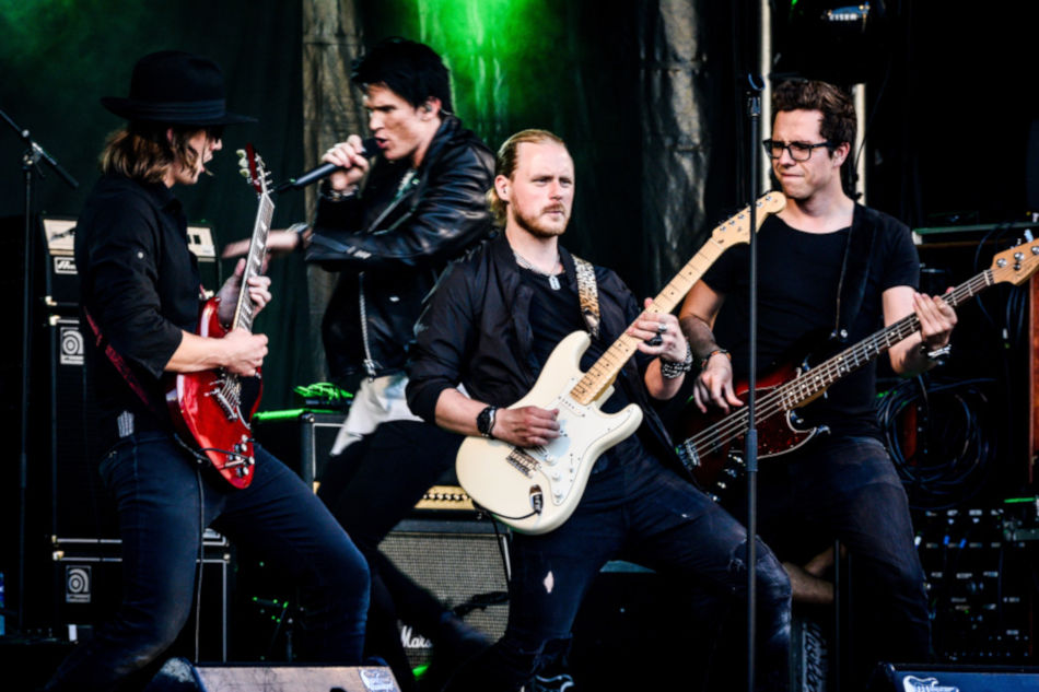 Four men rock band. One on electric guitar in front, and one on vocals, one on electric guitar, 