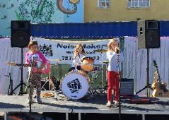 Little girls on stage playing guitar, drums, and singing