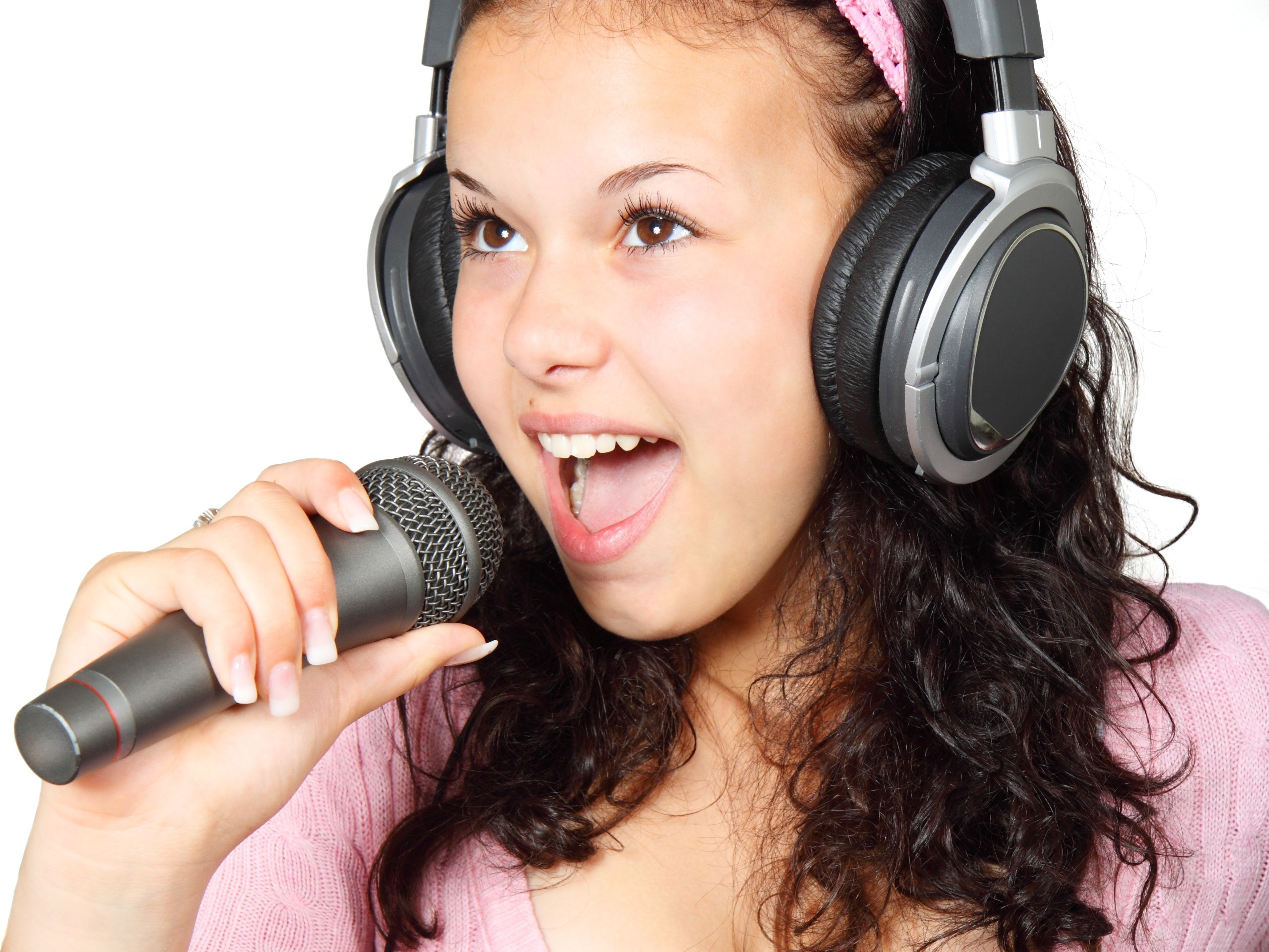 Teen female singer holding a microphone with headphones on